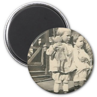 Two kids with a doll outside 2 inch round magnet