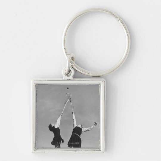 Two lacrosse players jump for the ball. keychain