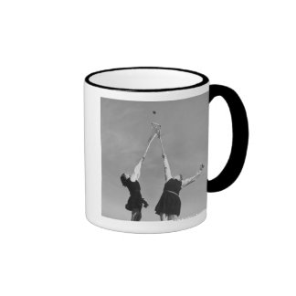 Two lacrosse players jump for the ball. coffee mugs