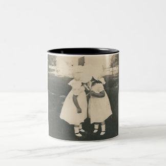Two little girls kissing mug