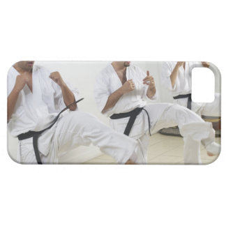 Two mid adult men with a young man practicing iPhone 5 cover