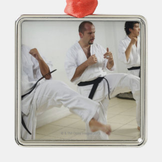Two mid adult men with a young man practicing metal ornament