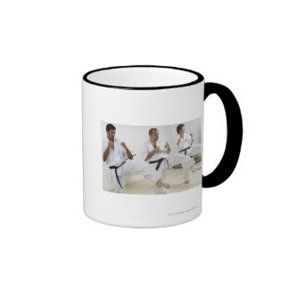 Two mid adult men with a young man practicing ringer mug