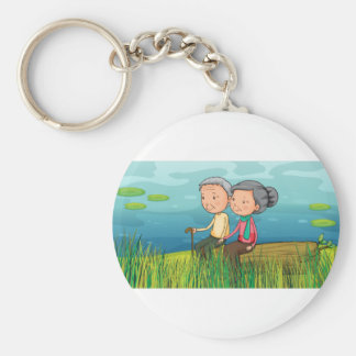 Two old people sitting near the lake basic round button keychain