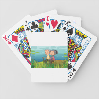 Two old people sitting near the lake bicycle playing cards
