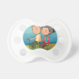 Two old people sitting near the lake pacifier