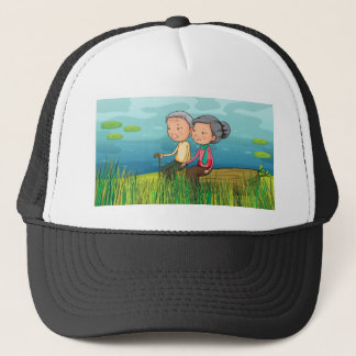 Two old people sitting near the lake trucker hat