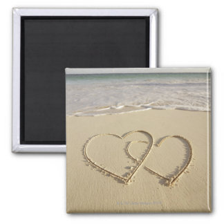 Two overlying hearts drawn on the beach 2 inch square magnet