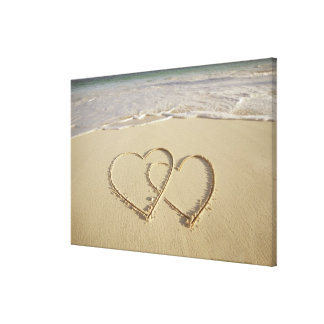 Two overlying hearts drawn on the beach canvas print