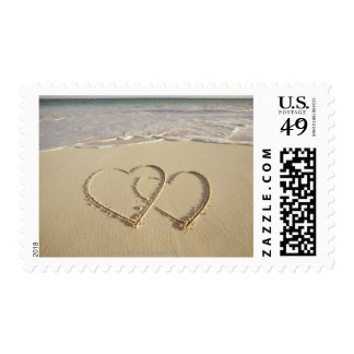 Two overlying hearts drawn on the beach postage stamp