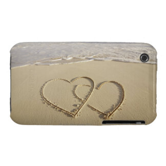 Two overlying hearts drawn on the beach with iPhone 3 covers