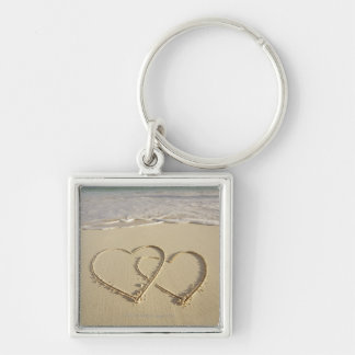 Two overlying hearts drawn on the beach with keychain