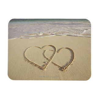 Two overlying hearts drawn on the beach with magnet