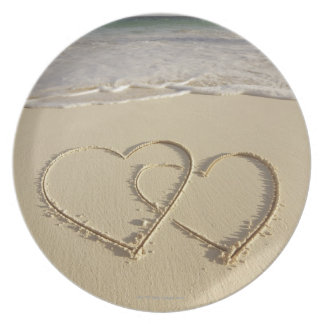 Two overlying hearts drawn on the beach with melamine plate