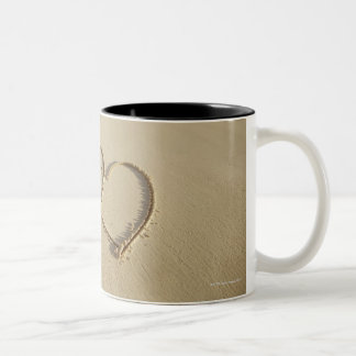 Two overlying hearts drawn on the beach with mug