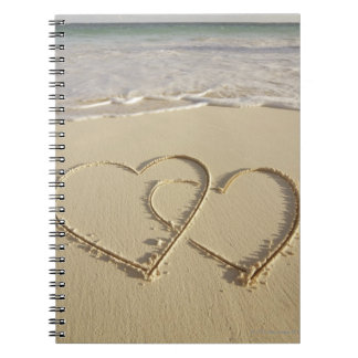 Two overlying hearts drawn on the beach with notebook
