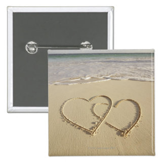 Two overlying hearts drawn on the beach with pinback button