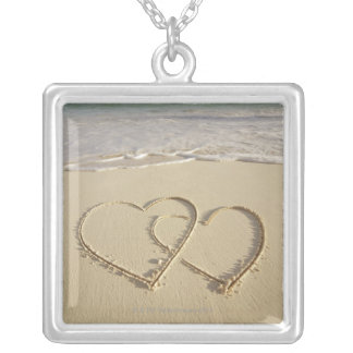 Two overlying hearts drawn on the beach with silver plated necklace