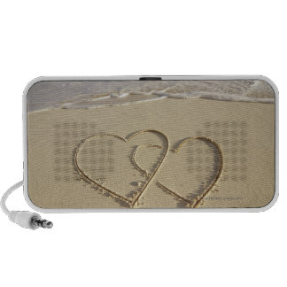 Two overlying hearts drawn on the beach with travel speakers