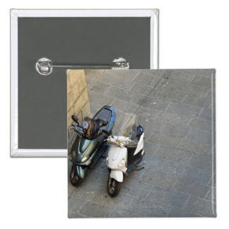 Two parked motor scooters by wall, Siena, Italy Pinback Button