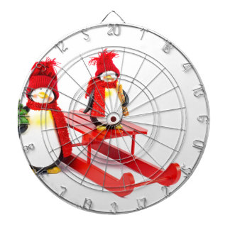 Two penguins with sleigh and christmas tree dartboard with darts