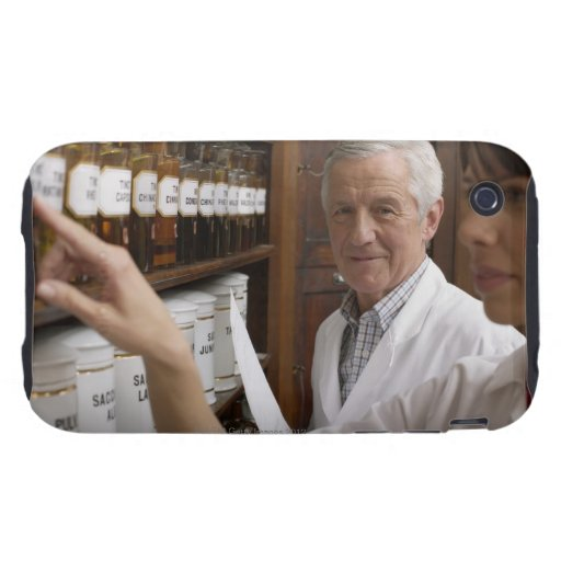 Two pharmacists in front of a shelf with tins tough iPhone 3 covers