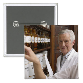 Two pharmacists in front of a shelf with tins pinback button