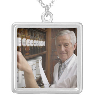 Two pharmacists in front of a shelf with tins silver plated necklace