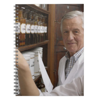 Two pharmacists in front of a shelf with tins spiral notebook