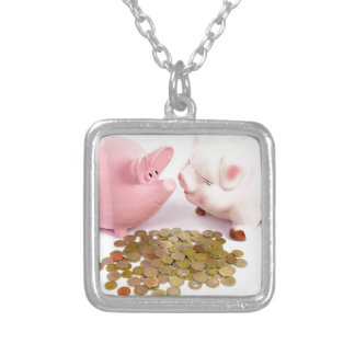 Two piggy banks with euro coins on white silver plated necklace