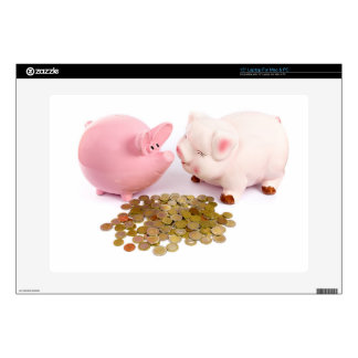 Two piggy banks with euro coins on white skin for laptop