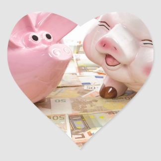 Two pink piggy banks on spread euro notes heart sticker