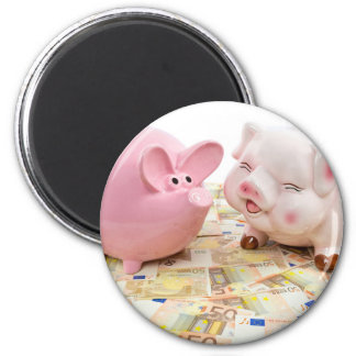Two pink piggy banks on spread euro notes magnet