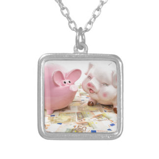 Two pink piggy banks on spread euro notes silver plated necklace