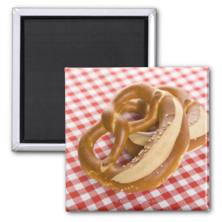 Two pretzel on checkered tablecloth magnet