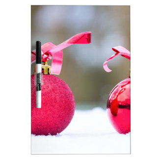 Two red christmas balls outside in snow dry erase board