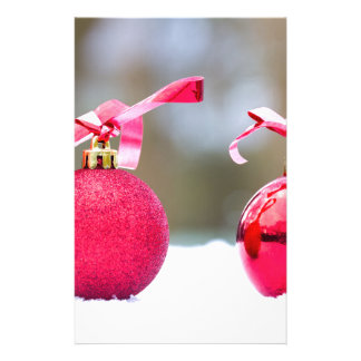 Two red christmas balls outside in snow stationery