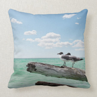Two seagulls sitting on a dead tree sticking out pillows