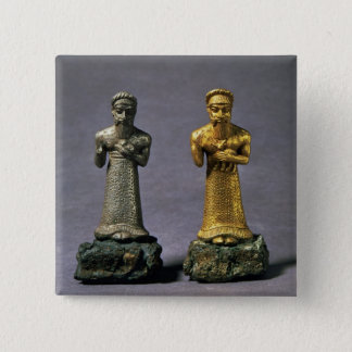 Two statuettes of men carrying offerings of goats, button
