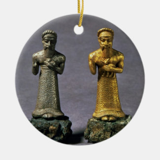 Two statuettes of men carrying offerings of goats, ceramic ornament