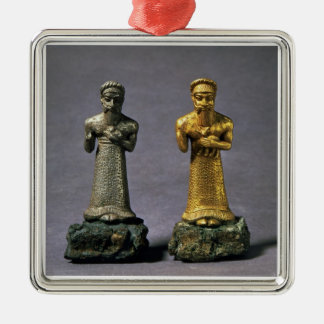 Two statuettes of men carrying offerings of goats, metal ornament
