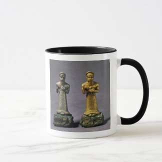 Two statuettes of men carrying offerings of goats, mug