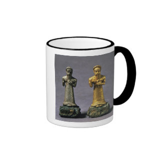 Two statuettes of men carrying offerings of goats, ringer coffee mug
