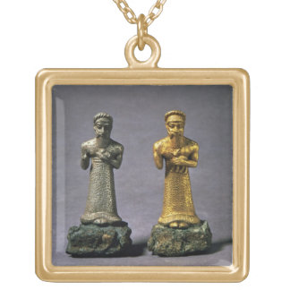 Two statuettes of men carrying offerings of goats, square pendant necklace