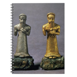 Two statuettes of men carrying offerings of goats, spiral notebook