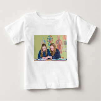 Two students learning with books in biology lesson baby T-Shirt