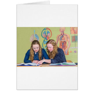 Two students learning with books in biology lesson card