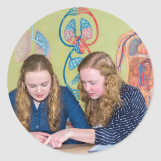 Two students learning with books in biology lesson classic round sticker