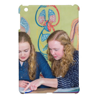 Two students learning with books in biology lesson iPad mini cover