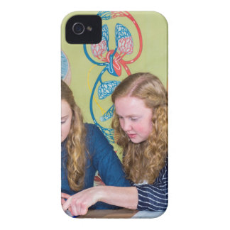 Two students learning with books in biology lesson iPhone 4 cover